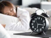 Womean sleeping with clock